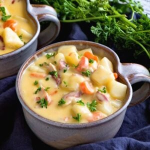Two bowls of cheesy bacon potato soup on a navy kitchen towel with fresh parsley