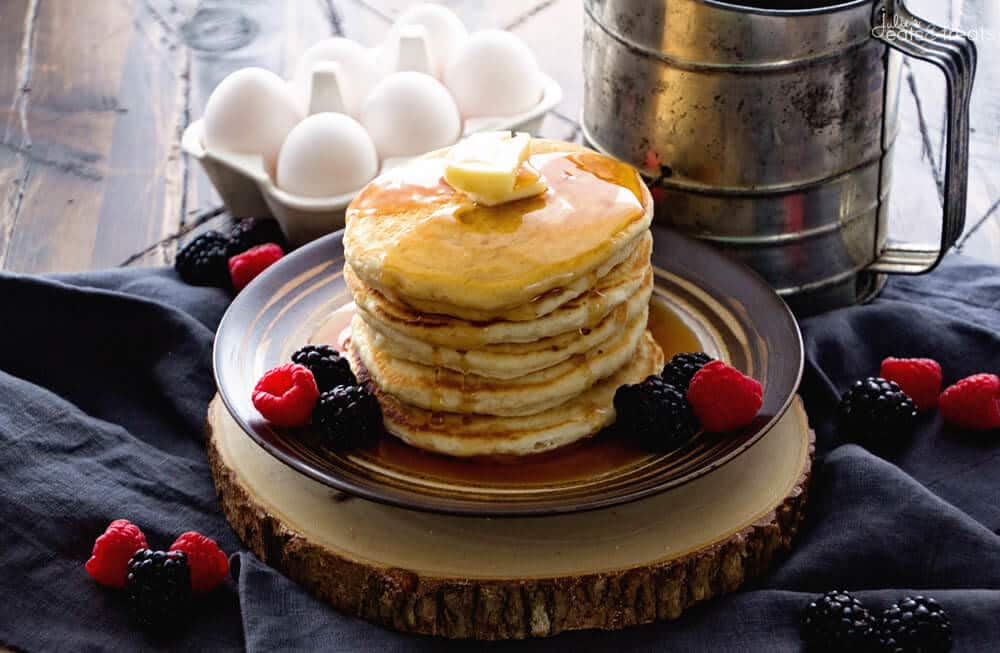 Plate with stack of pancakes topped with butter and syrup and berries on the side