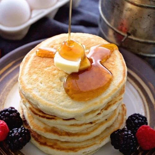 Stack of homemade pancakes with syrup being poured on them