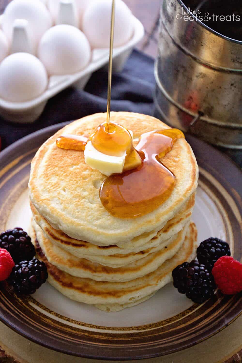 Stack of pancakes with butter on top and syrup being poured onto them