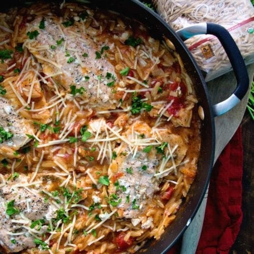 Skillet of light one pot Italian salmon and orzo next to a wooden spoon and a package of orzo