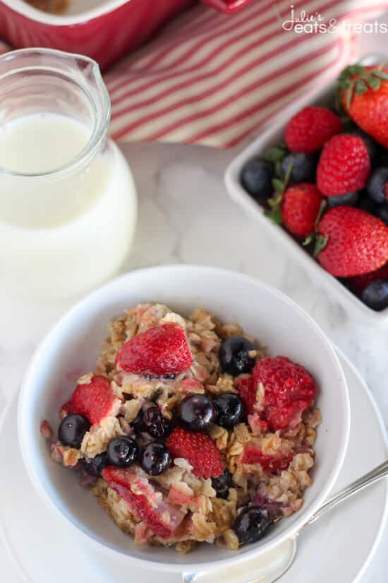 Berry Oatmeal Bake in white bowl with berries and milk.