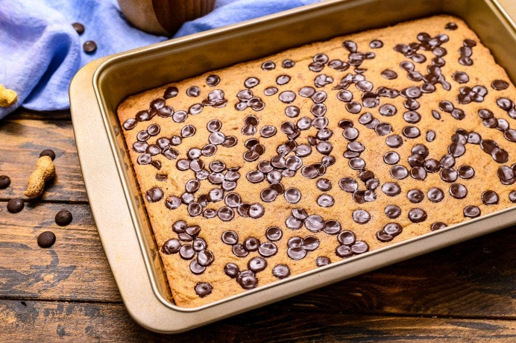 Pan of baked bars on wooden background with blue napkin in background