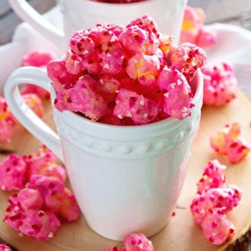 Two white mugs of puff corn valentines snack mix spilling out onto the wood platter they are on