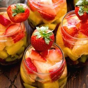 Overhead image of four stemless wine glasses of rainbow sangria containing slices of kiwi, pineapple, and strawberry