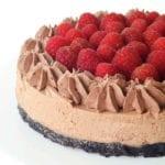 A raspberry chocolate cheesecake on a white cake stand