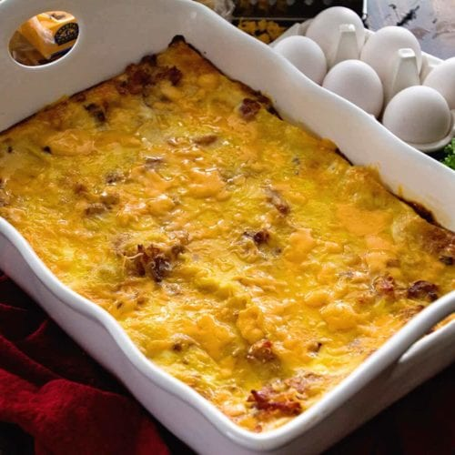 Ham and cheese overnight breakfast lasagna in a white casserole dish sitting on a red kitchen towel next to six eggs, an onion, and fresh parsley
