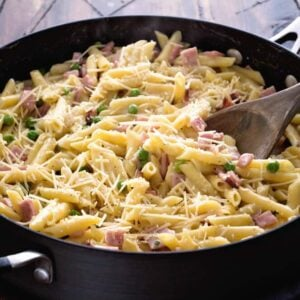 Skillet pan of one pot ham and penne pasta with a wooden spoon in it