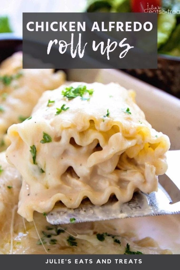 Chicken alfredo roll up on a spatula being lifted out of a white casserole dish
