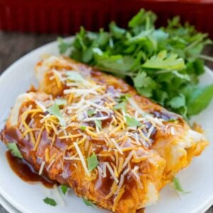 Two beef and potato enchiladas and cilantro on a white plate in front of a red baking dish of enchiladas