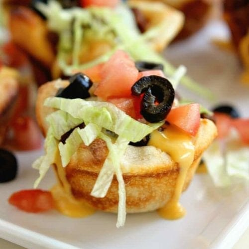 Taco muffin cups on a white square plate topped with cheese, lettuce, tomatoes, and olives