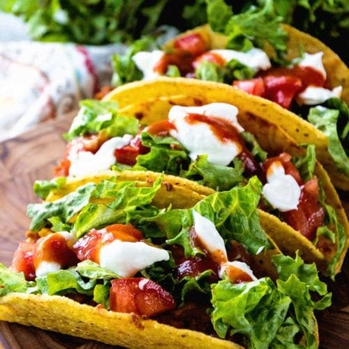 Three easy stuffed tacos on a wood cutting board