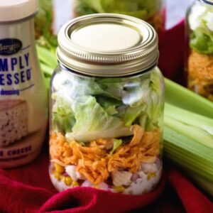A mason jar of buffalo chicken salad on a red towel with celery and a jar of blue cheese dressing
