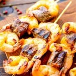 Grilled steak and shrimp kabobs on a cutting board