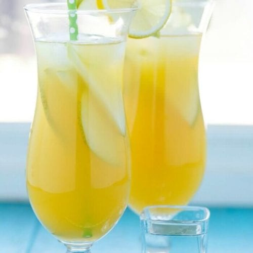Two glasses of pineapple fruit cocktail with lemon slices on the rim