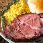 Slice of smoked prime rib with corn, a dinner roll, and rosemary on a plate