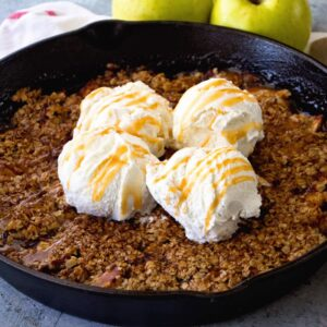 A cast iron skillet of grilled caramel apple crisp topped with four scoops of vanilla ice cream and caramel sauce