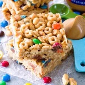 Two no bake peanut butter cereal bars stacked on a piece of wax paper along with m&m's, peanuts, measuring spoons, and a jar of peanut butter