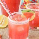 Two glasses with sugared rims of spiked watermelon lemonade and lemon and watermelon slices on the rim sitting on a burlap place mat