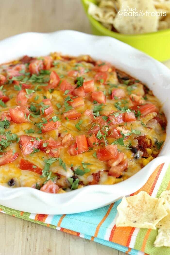 Southwestern Bean & Cheese Dip - A quick oven-baked dip made with layers of cream cheese, salsa, black beans, corn, melted cheese, tomatoes, and cilantro.