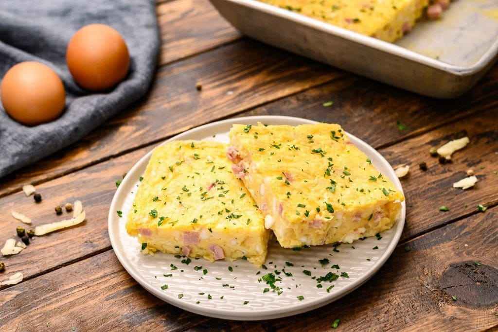 White plate with two pieces of baked omelet on it