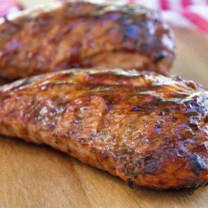 Two grilled bbq turkey loins on a wood cutting board