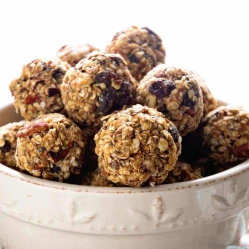 White bowl of oatmeal raisin energy balls