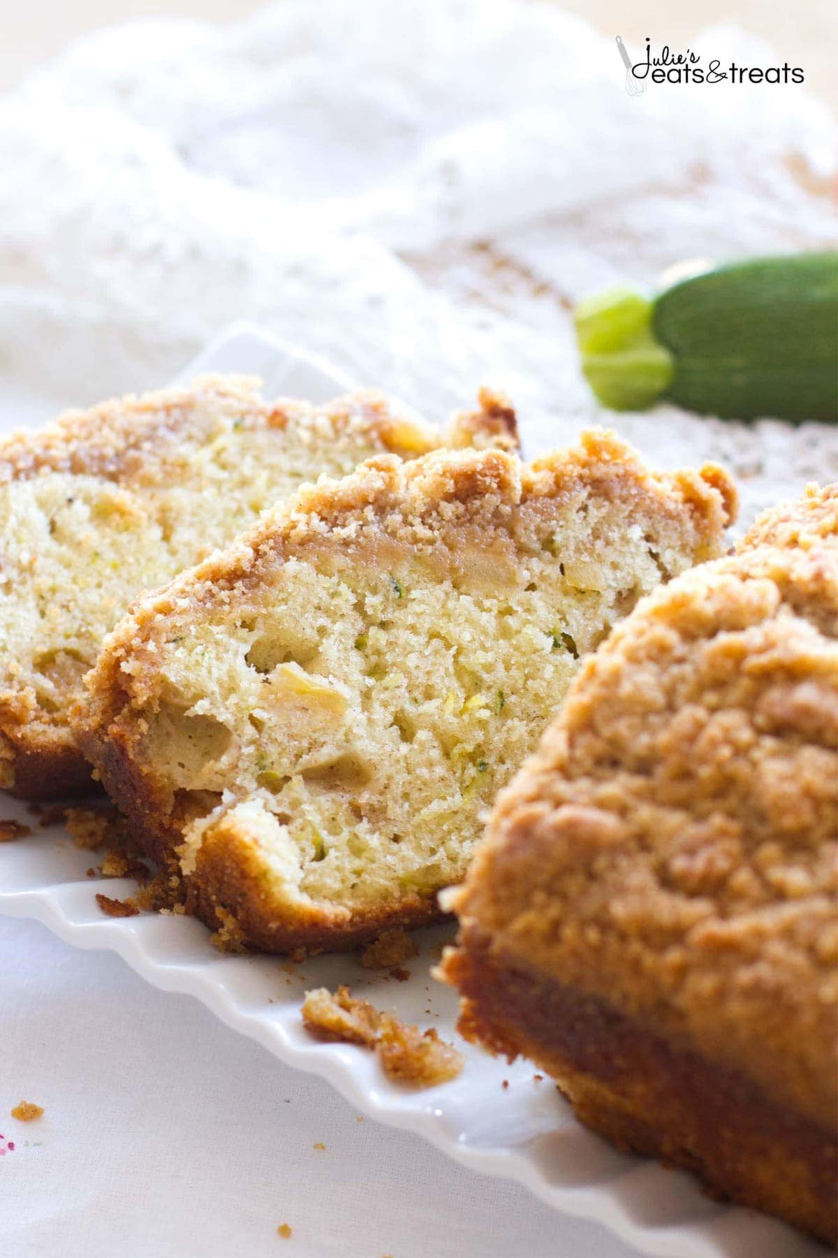 Sliced Crumb Apple Zucchini Bread ~ Easy, Quick Bread Recipe Filled with Fresh Grated Zucchini and Sweet Apples then Topped with Cinnamon Brown Sugar Crumb Topping on a white cloth.