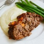 A slice of cheesy meatloaf on a white plate with mashed potatoes and green beans
