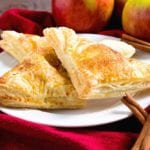 Three easy apple turnovers on a white plate sitting on a red kitchen towel with cinnamon sticks and apples