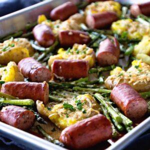 A metal sheet pan of sausage, smashed potatoes, and asparagus