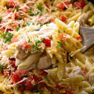 Wooden spoon scooping pasta out of a skillet full of one pot cajun chicken pasta