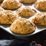 A muffin tin of skinny peanut butter banana muffins sitting on a kitchen towel along with berries