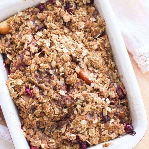 A white rectangular baking dish of apple cranberry crisp on a wood table