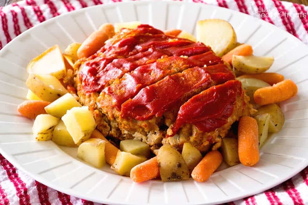 Slow Cooker Meatloaf Recipe on a white platter surrounded by potatoes and carrots.
