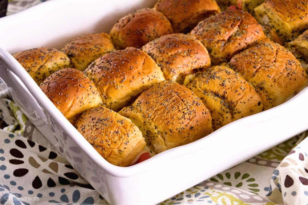 White casserole dish with turkey sliders topped with poppy seeds in them.