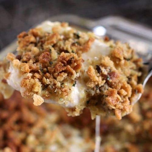 A spatula lifting a cheesy chicken stuffing casserole piece out of a baking dish