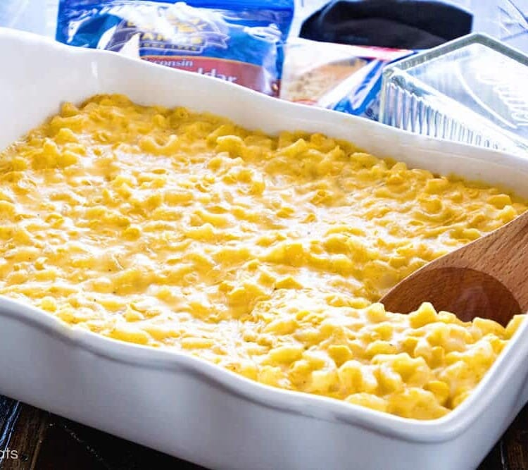 Creamy corn macaroni and cheese casserole in a white baking dish with a wood spoon in it and two bags of shredded cheese and a butter dish behind it