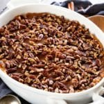 A white oval baking dish of light sweet potato casserole on a navy blue kitchen towel with cinnamon sticks, pecans, and a wood spoon
