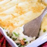 Turkey shepherds pie in a white casserole dish with a wood spatula in it