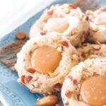 Caramel thumbprint cookies on a blue plate with almonds