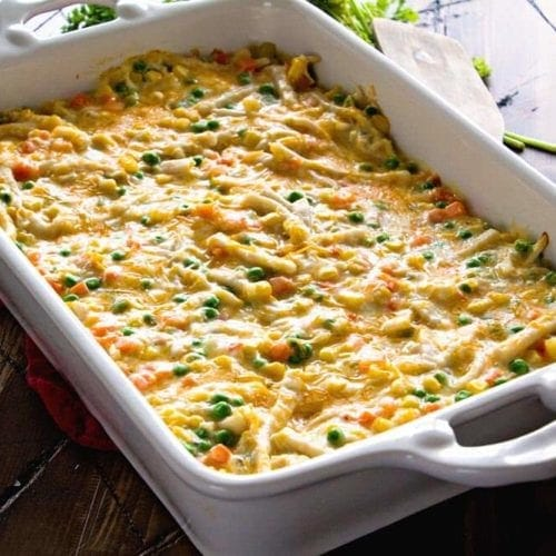 Cheesy chicken noodle casserole in a white baking dish