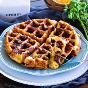 A loaded bacon, egg, and cheese waffle on a blue plate sitting on a white plate next to a pitcher of cream, a bowl of shredded cheese, a bundle of fresh parsley, and a carton of eggs