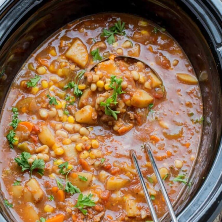 Slow cooker beef and vegetable soup in a black crock pot with a silver ladel