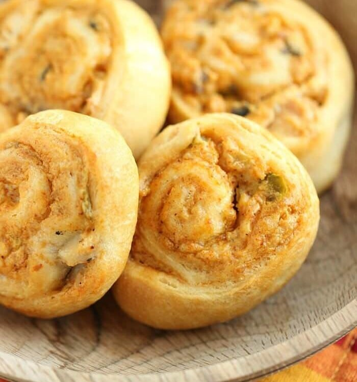 Four crescent chicken taco pinwheels in a wood bowl