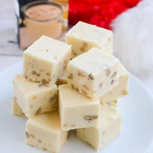 Stacks of eggnog fudge on a white plate in front of a Christmas stocking and a carton of egg nog