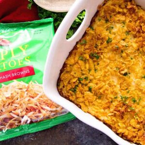 Cheesy chicken hash brown casserole in a white baking dish next to a bag of simply potatoes hash browns