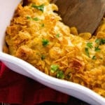 White baking dish of cheesy hash brown chicken casserole with a wooden spoon