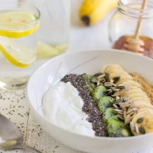 Yogurt, seeds, kiwi, and banana in a white bowl on a table with a spoon, two glasses of lemon water, a banana, and a jar of honey