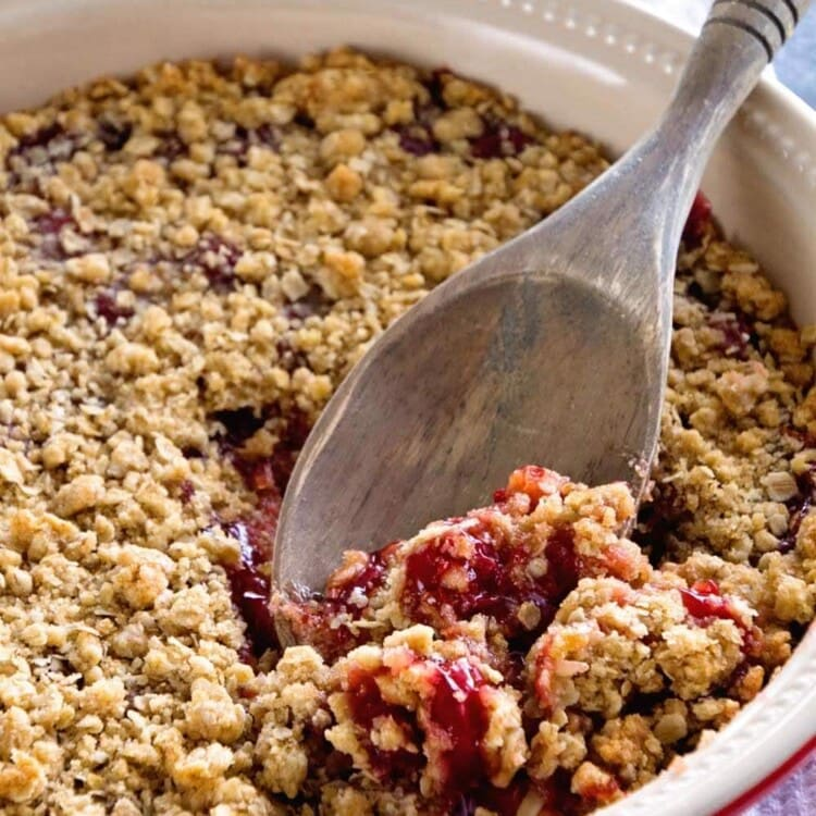 A white and red circular baking dish of cherry crunch dessert with a wooden spoon in it